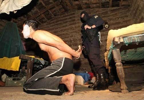 Foto de archivo del arresto de un supuesto miembro de pandillas en su vivienda. La escena evidencia la pobreza en la que viven la mayoría de pandilleros.