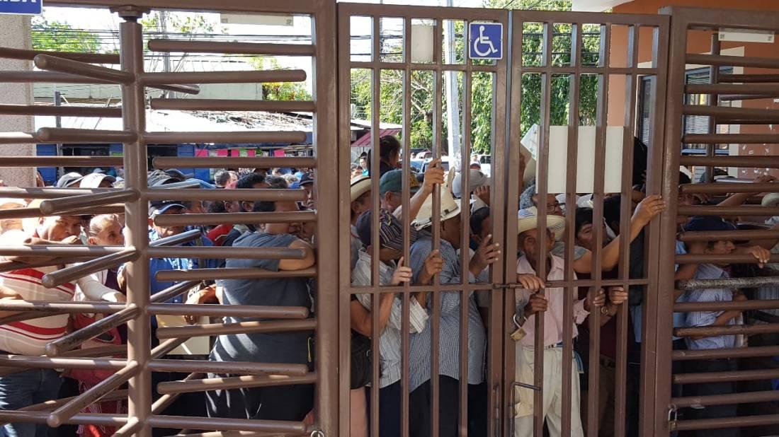 Un grupo de veteranos de la Fuerza Armada se agolpan al portón de entrada del Ministerio de Gobernación para entregar documentos que los acreditan como veteranos del conflicto 1980-1992